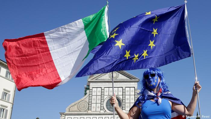 Flags of Italy and the EU held by a demonstrator in Florence