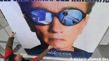 Ein Messebauer streicht am Freitag (27.02.2009) auf dem Messegelände in Hannover ein Werbeplakat des diesjährigen CeBIT- Partnerlands Kalifornien zurecht, auf dem der Gouverneur des Landes, Arnold Schwarzenegger, zu sehen ist. Mit den Themenschwerpunkten Green IT, elektronische Gesundheitssysteme (eHealth), IT-Sicherheit und Webciety will sich die weltgrößte Computerfachmesse CeBIT in diesem Jahr auch in der Krise behaupten. Vom 03. bis 08. März 2009 werden etwa 4300 Aussteller aus 69 Ländern ihre Produkte in Hannover präsentieren. Foto: Jochen Lübke dpa/lni +++(c) dpa - Bildfunk+++
