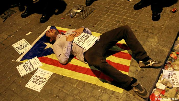 A pro-separatist demonstrator lies on a Catalan flag, clutching a poster that reads: We vote to be free
