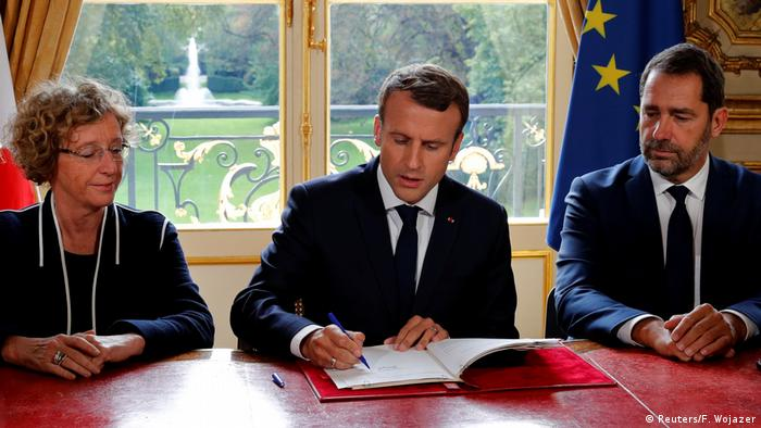 French President Macron signs labor reform measures Friday at the Elysee Palace, flanked by his Minister of Labour Muriel Penicaud and government spokesman Christophe Castaner.