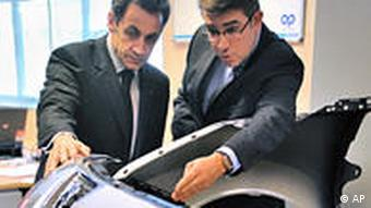 Sarkozy looks at a Peugeot with another man