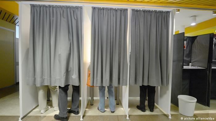 People in voting booths in Germany