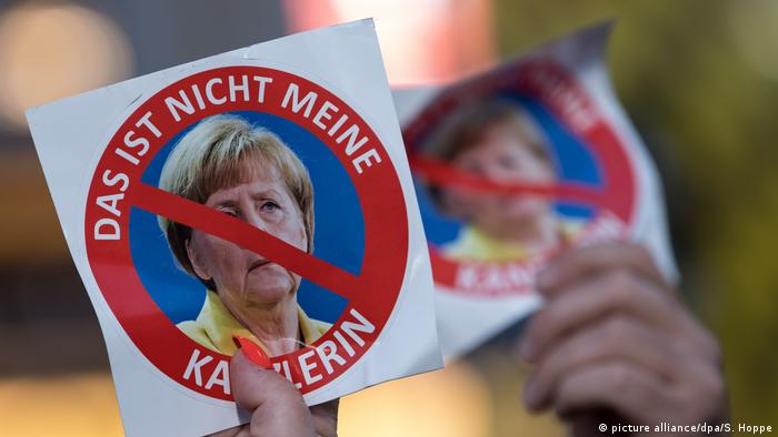 A placard with a picture of Merkel and line through her face and a caption that says, not my chancellor.