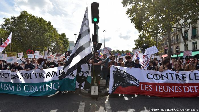 Protesters in Paris march with banners, placards and flags against President Macron's labor reforms.