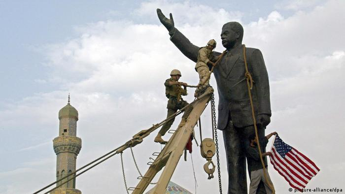 US Marines use heavy equipment as they prepare to bring down a statue of Saddam Hussein in Baghdad in 2003.