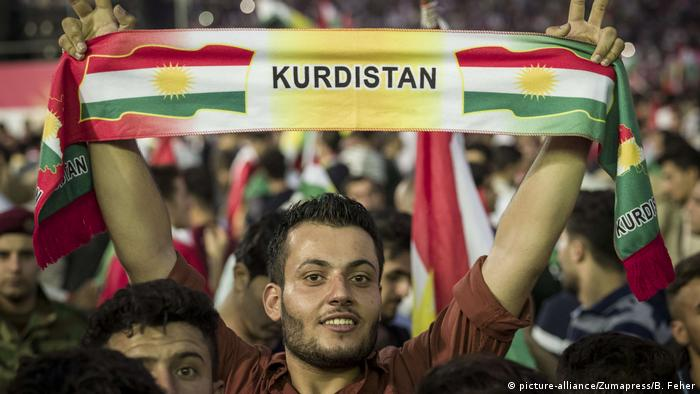 A person smiling and holding a banner that reads Kurdistan at a rally