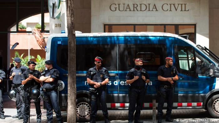 Several Mossos d'Esquadra police stand guard during a pro-independence protest in Barcelona.
