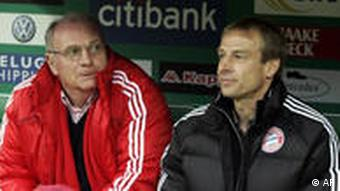 Juergen Klinsmann and Uli Hoeness sitting on the bench during soccer match