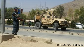 Afghan police secure the street in Kabbul after a suicide car bomb