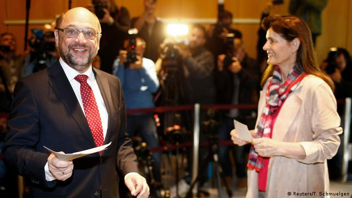 Martin Schulz and his wife hold ballots at a polling station
