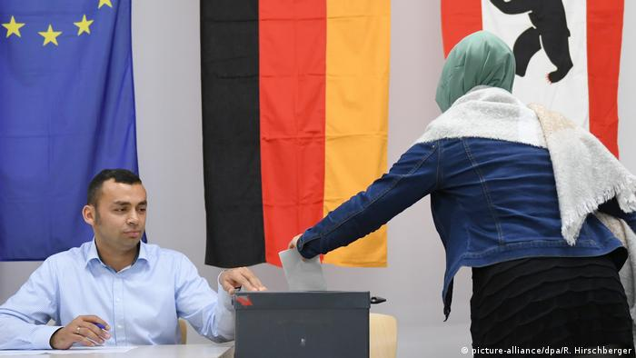 A woman in a headscarf puts her vote in the ballot box in Berlin Kreuzberg.