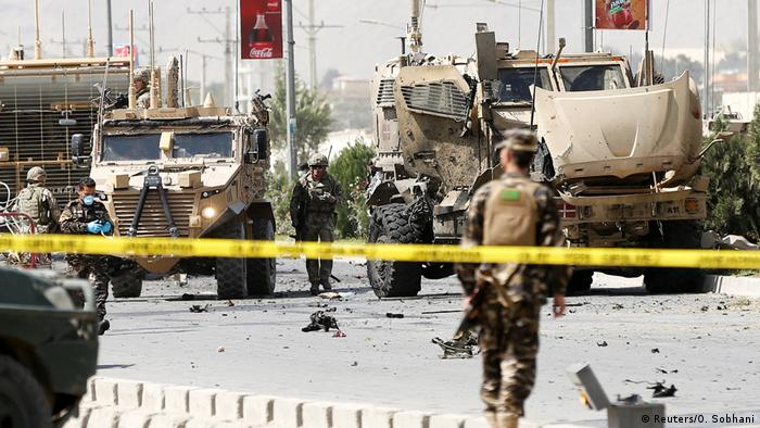 Soldiers secure the area where a suicide car bomb hit a NATO convoy