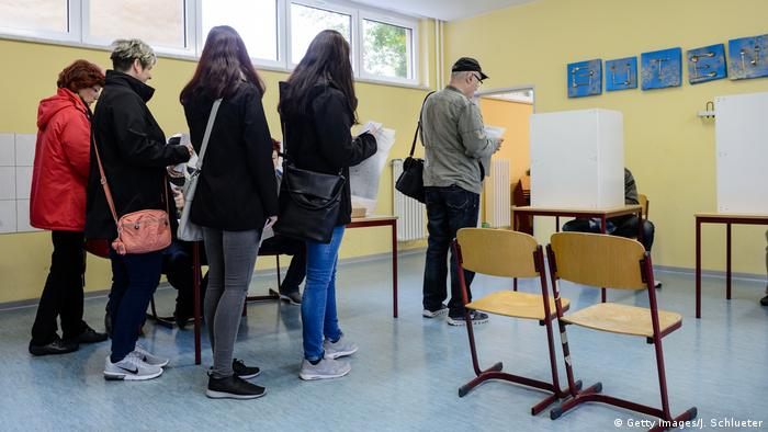 People are waiting for the vote at a polling station during German federal elections on September 24, 2017