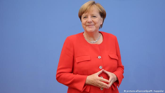 Merkel wearing a red suit jacket and holding her hands in a diamond shape