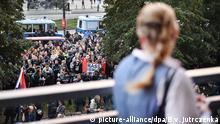 Eine AfD-Anhängerin schaut während der Wahlparty in Berlin vom Balkon auf Proteste gegen die Partei