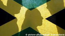 ARCHIV - ILLUSTRATION - Eine Frau und zwei Männer stehen am 20.09.2005 hinter der Landesfahne von Jamaika in den Farben schwarz, gelb und grün. Die Grünen in Berlin hatten es sich anders gewünscht, zumindest die meisten. Aber die Entscheidung von Saarlands Grünen-Chef Ulrich für eine «Jamaika»-Koalition in seiner Heimat hat der Partei neue Möglichkeiten eröffnet. Am Mittwoch (14.10.2009) wollen sich CDU, FDP und Grüne in der Saarbrücker Staatskanzlei erstmals über den Fahrplan für die Koalitionsverhandlungen unterhalten. Foto: Frank Rumpenhorst dpa/lrs (zu dpa-Korr. Jamaika eröffnet Grünen neue Reisemöglichkeiten vom 13.10.2009) +++(c) dpa - Bildfunk+++ | Verwendung weltweit