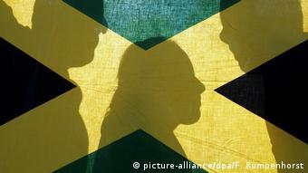 Тени трех человек на фоне флага Ямайки