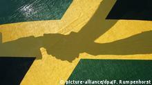 ARCHIV - ILLUSTRATION - Drei Hände vereinigen sich am 20.09.2005 in Frankfurt hinter der Landesfahne von Jamaika in den Farben schwarz, gelb und grün. (zu dpa Grüner Spagat: Abgrenzen ohne Ausgrenzen vom 15.09.2017) Foto: Frank Rumpenhorst/dpa +++(c) dpa - Bildfunk+++   Verwendung weltweit