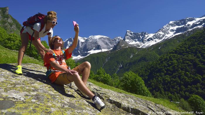 Dois turistas fazem um selfie no parque nacional da Vanoise, na França