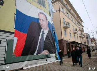 People walk along Vladimir Putin Avenue past a wall-sized portrait of Putin in downtown Grozny