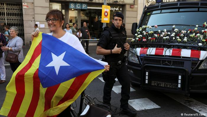 A woman holds a Catalan separatist flag in front of a Mossos police van REUTERS/Susana Vera