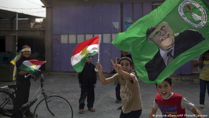 Kids run around with the Kurdish flag after the referendum