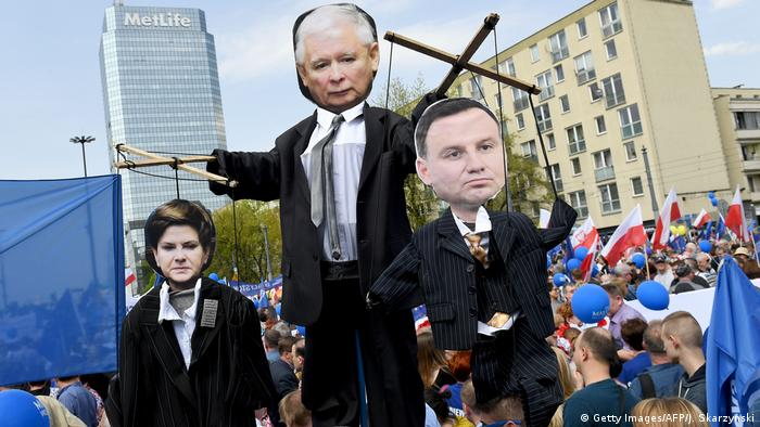 Demonstrators hold cartoons of leader of PiS party Jaroslaw Kaczynski, Prime minister Beata Szydlo and President Andrzej Duda