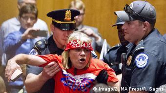 Two policemen restraining a women inside Capitol Hill, Washington (Imago/ZUMA Press/R. Sachs)
