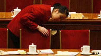 Chinese ushers looks under the tables after delegates leave at the end of the opening session of the Chinese People's Political Consultative Conference held at the Great Hall of the People in Beijing, China,Tuesday, March 3 , 2009. Economic troubles, including creating jobs and ensuring a massive stimulus package is properly used, are the main concerns for China's main legislative advisory body meeting this week. (AP Photo/Ng Han Guan)