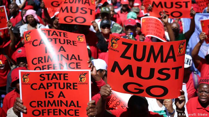 Protestors hold signs against corruption in South Africa