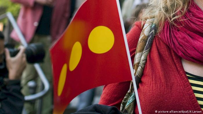 A women holds a red flag with three yellow spots (picture-alliance/dpa/J.N.Larsen)