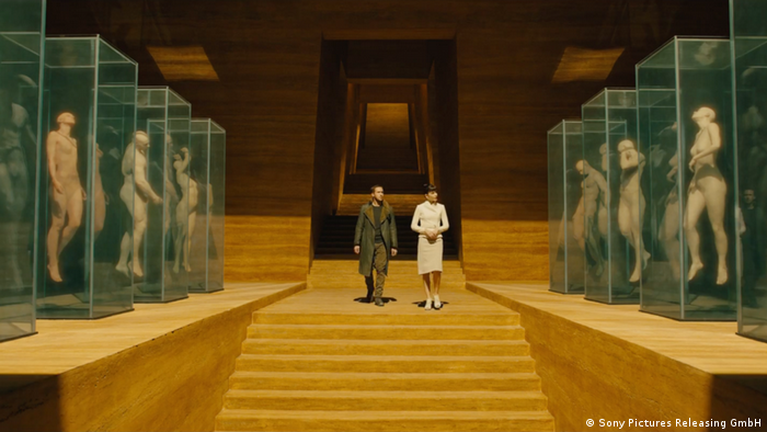 A film still from Blade Runner 2049 with two actors walking down the stairs in a museum and observing human forms in display cases (Sony Pictures Releasing GmbH)