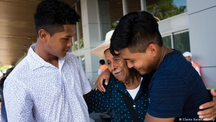 Lizandro and Diego Claros Saravia hug their relative