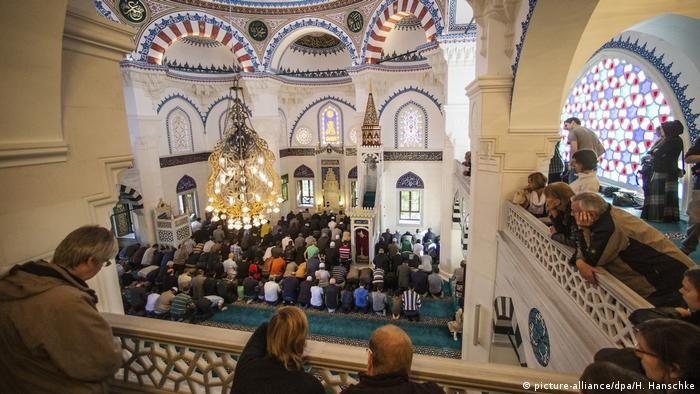 Visitors at a mosque observe daily prayer