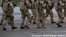 Soldaten der Bundeswehr gehen am 25.09.2017 in Munster (Niedersachsen) bei der Vorbereitung zu der Informationslehrübung «Landoperationen 2017» auf einem Platz entlang. Foto: Philipp Schulze/dpa   Verwendung weltweit