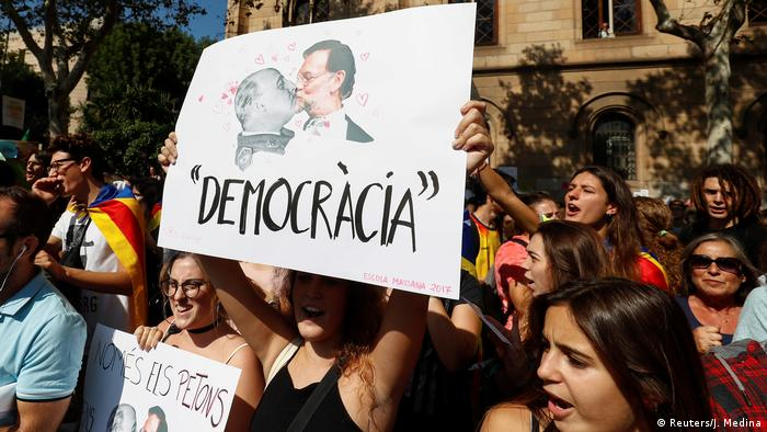 Young girl holds up placard with pictures of Rajoy and Franco kissing (Reuters/J. Medina)