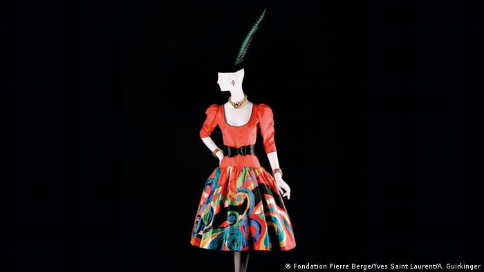 A mannequin wears a dark hat with a tall feather and a read dress with a vibrantly colored skirt and black belt.