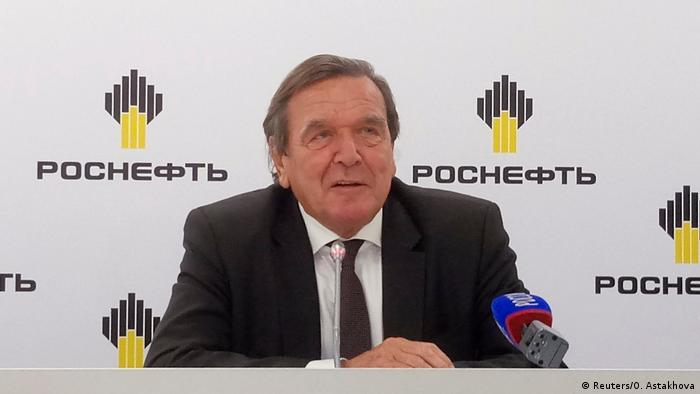 Schröder sitting in front a backdrop reading Rosneft (Reuters/O. Astakhova)