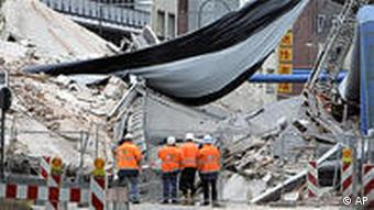 workmen standing in front of collapsed building