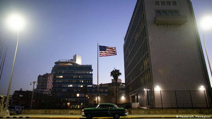 A vintage car passes by in front of the US embassy in Havana