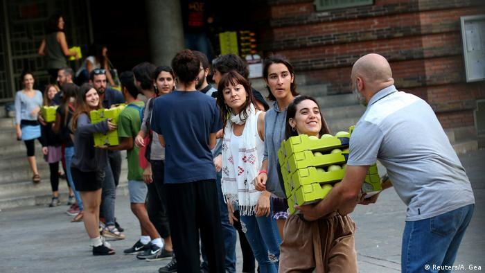 Activists form a human chain to pass electoral supplies into a school (Reuters/A. Gea)
