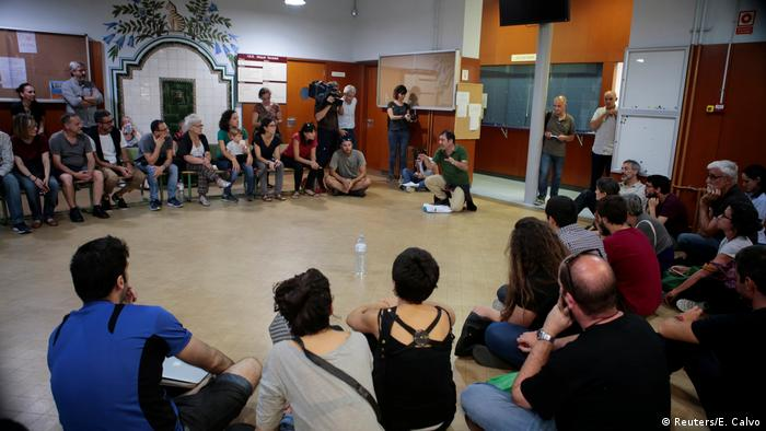 A group of activists sit in a hall at Barcelona's Miquel Tarradell high school