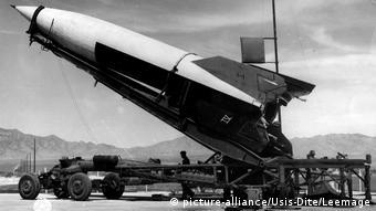 Foto em preto e branco mostra um foguete na rampa de lançamento