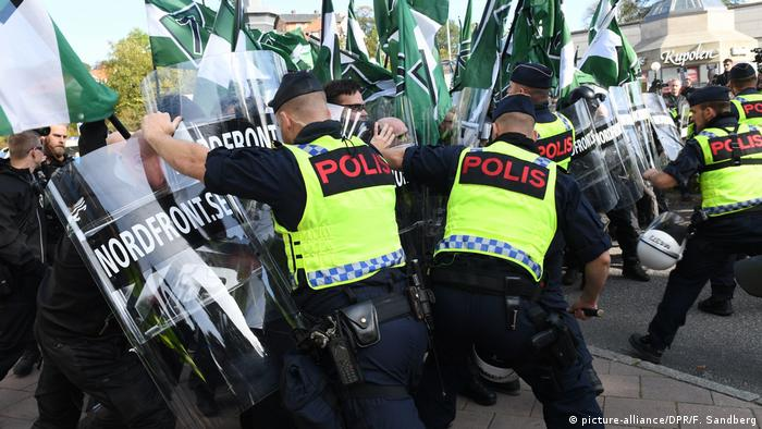 Neo-Nazis wielding transparent shields and their green and white flags clash with police in Goteborg, Sweden.