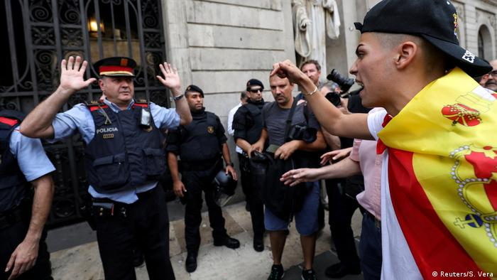 Youth wearing Spanish flag shouts at a police officer in Barcelona (Reuters/S. Vera)