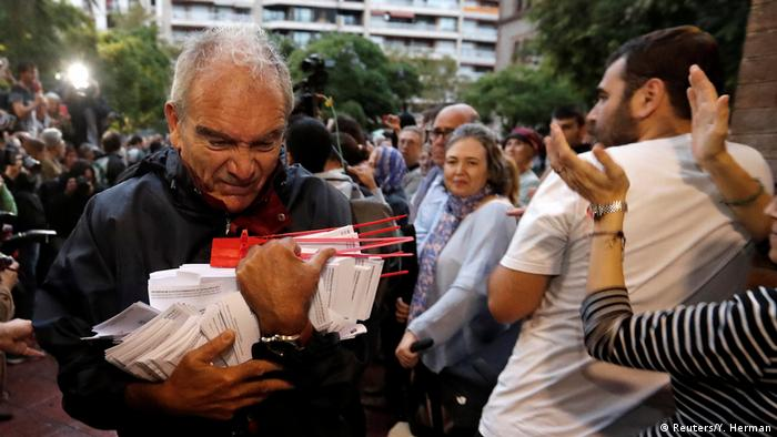 An elderly man carries ballots in his arms (Reuters/Y. Herman)