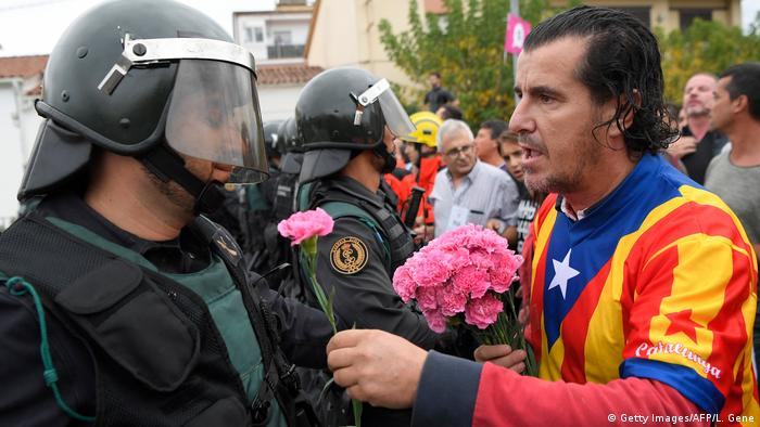 A man wearing Catalan colors offers a flower to a member of the Civil Guard (Getty Images/AFP/L. Gene)