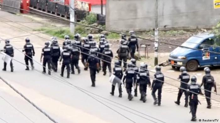 Riot police walk along a street in a Cameroonian city