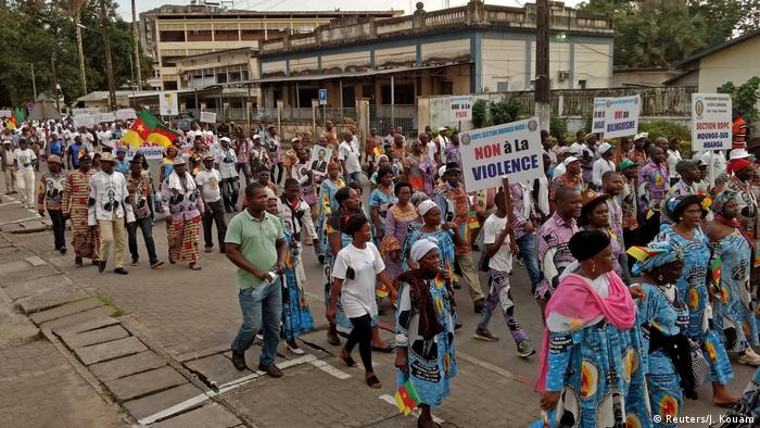 Demonstrators carrying placards march along the streets of Douala in Cameroon