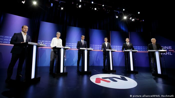 Six candidates stand in a semi-circle at podiums in a darkened TV studio